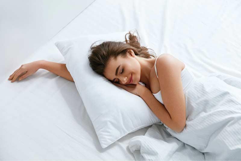 Junge Frau liegt in einem Bett und erholt sich