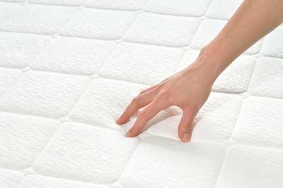 Hand streicht über eine weisse Matratzenauflage von Sweet Dreams