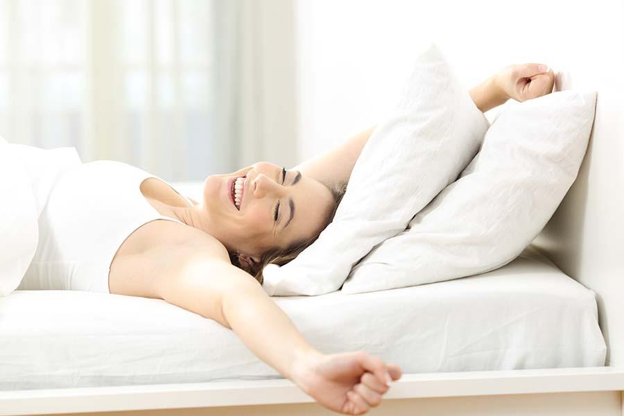 Frau ist am aufwachen und streckt sich im Bett